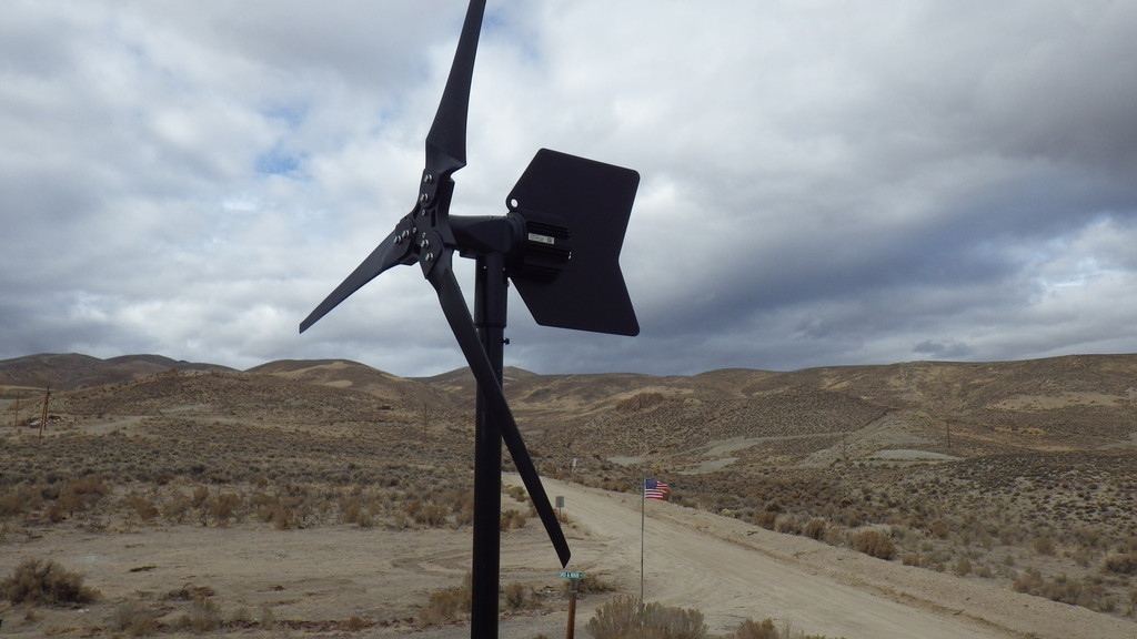APRS World's WT14 wind turbine with American flag in the background.
