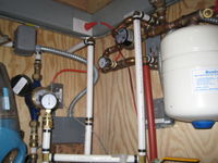 Fuzzy picture of flat plate heat exchanger, expansion tank, glycol circulation pump, water meter, and water pressure gauge.