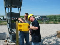 James of APRS World shows Patrick of Tower Tech the data logger installation steps.
