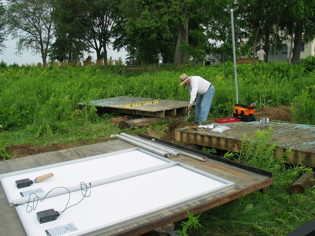 Jim Heaser works on leveling the old decks that will serve as the base for the solar panels.