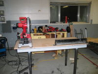 Currently there is a bench grinder, drill press, and vise also on the table. Eventually an outfeed and stop for the dry cut saw will be fabricated. Note the high quality rattle can primer. I got bored and sick of primering before getting to the legs. Fortunately they still have tons of metal protectant left of them...