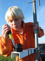 Kobi Dansingburg levels the Davis solar radiation sensor at the Wiscoy weather station test site.