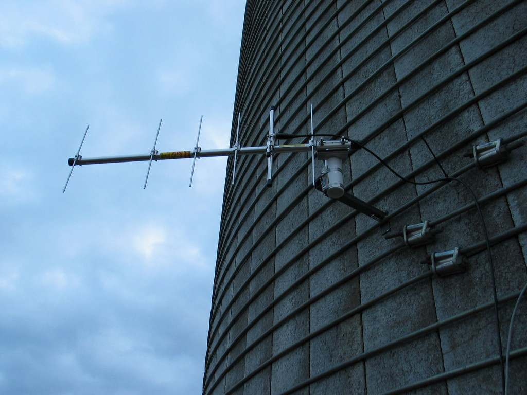 "Example bracket for mounting an antenna or anemometer to a silo band. This was created in a few minutes by welding some scrap 1"" square tubing, plate, and the u-bracket. 1.5"" PVC pipe is hose clamped into the bracket. That could be an anemometer, wind vane, or tee."
